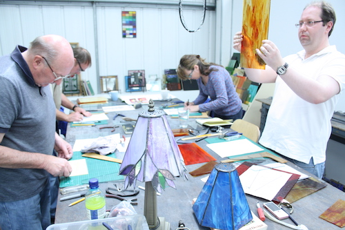 Students learning the techniques of making stained glass and fused glass